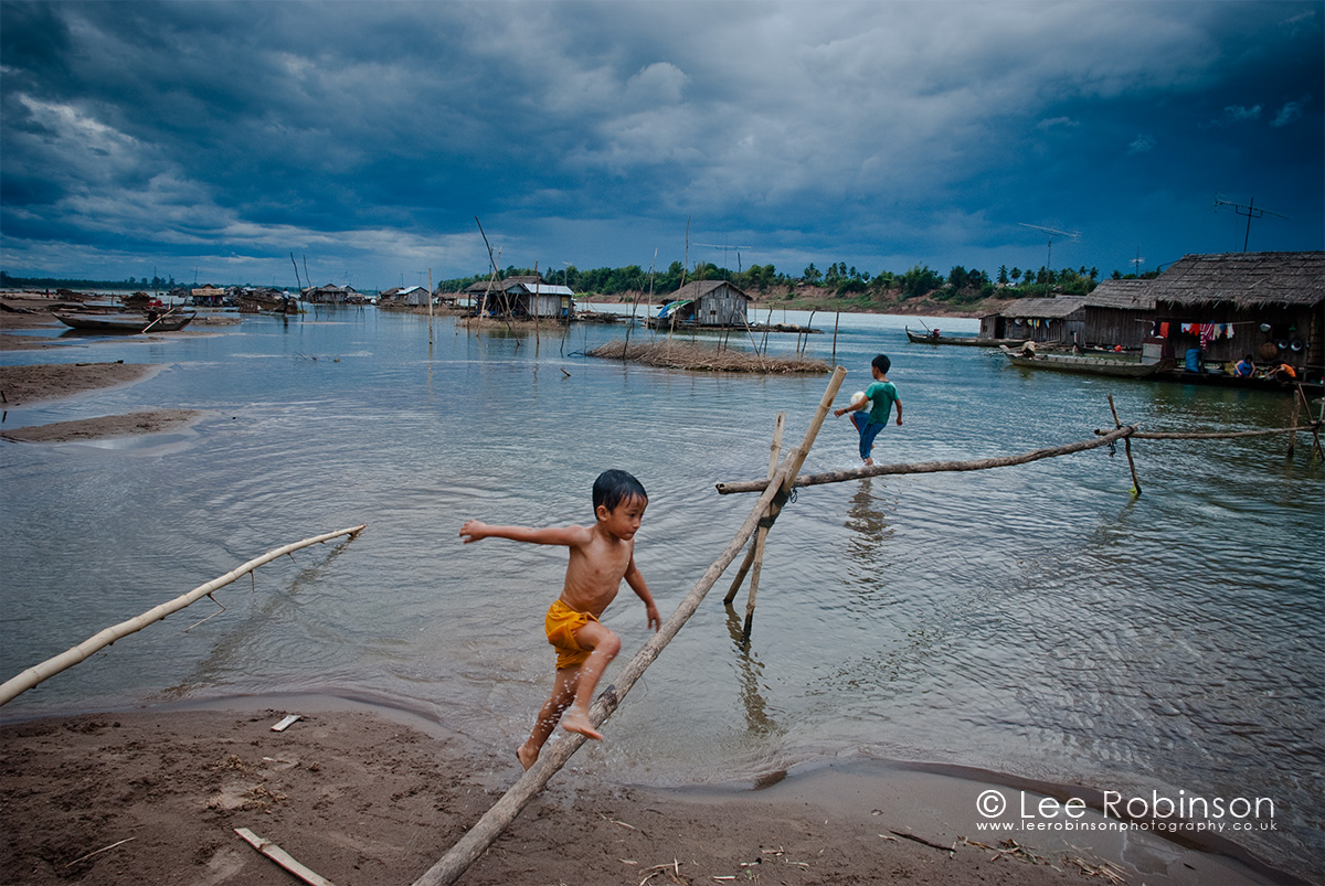 Photography by lee robinson, of Children playing in the water, Koh Trong floating village, Kratie Cambodia