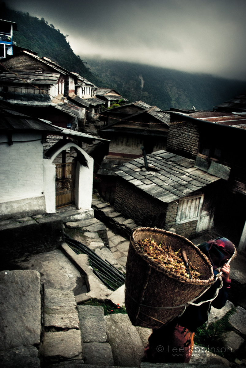 Lee robinson photography, photo of old lady carrying basket in village, Nepal